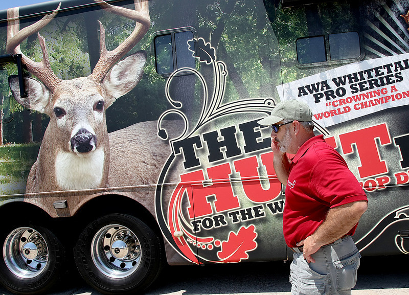 Greg Koch, inspects the motor coach he and his family will be using for the next Seven months to travel across America to find the best 40 deer hunters.