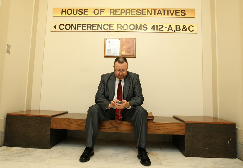 Mark Newman textx from the fourth floor of the State Capitol early Friday morning on the last day of session. PHOTO BY MAIKE SABOLICH
