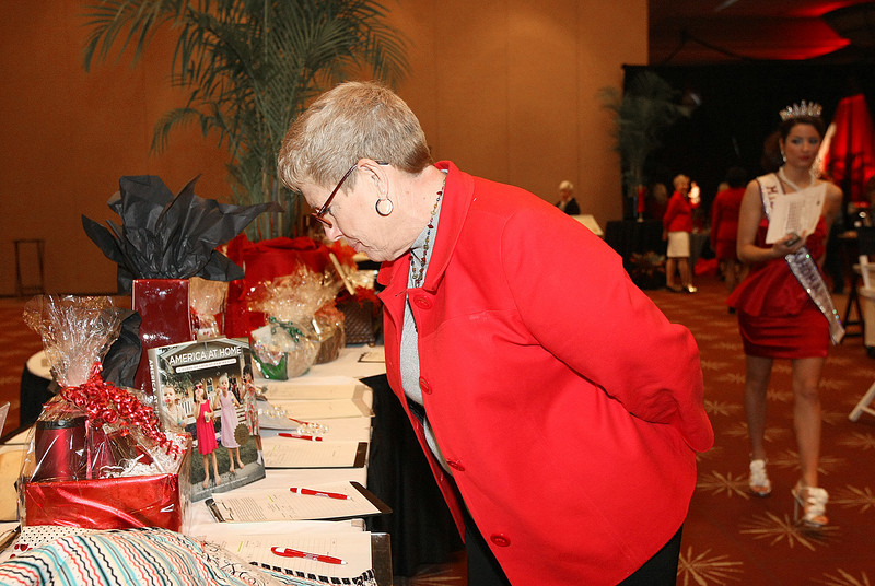 Cindy Davidson checks out silent auction items at the Go Red For Women event at the Cox Center Friday. PHOTO BY MAIKE SABOLICH