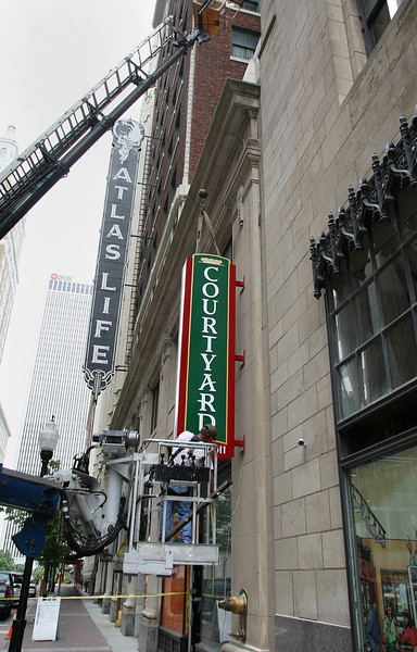 Workmen install the Courtyard by Marriott sign on the side of the Atlas Life Building in downtown Tulsa.
