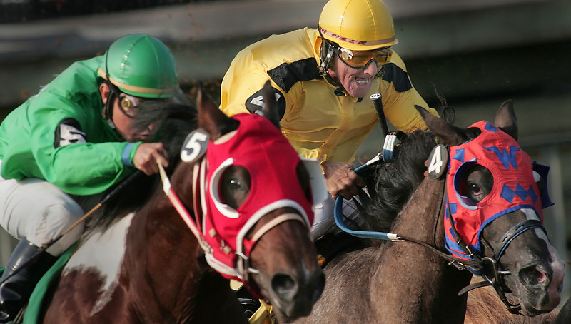 Jockeys Benny Landeros (green silks) and Tony Bennett urge their mounts forward during the 3rd race of Fair Meadows opening day.  Fair Meadows opened it's two month long racing season in Tulsa this Thursday.