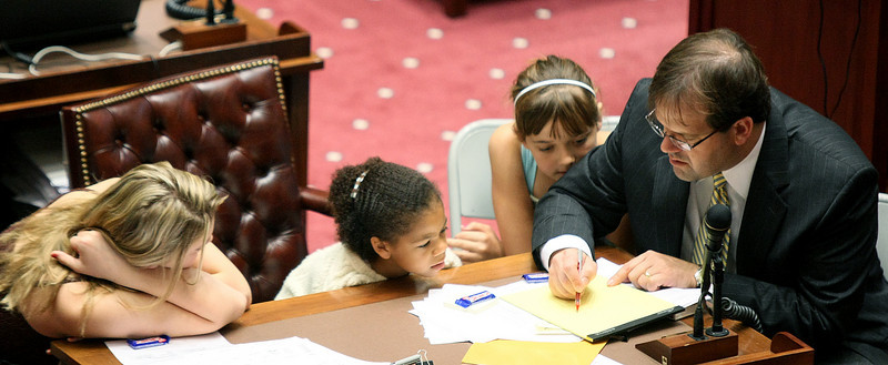 Senator Patrick Anderson spends time with his two daughters Kate, left, and Lauren, right, and guest Esther, middle, on the Senate floor on the last day of session Friday. PHOTO BY MAIKE SABOLICH