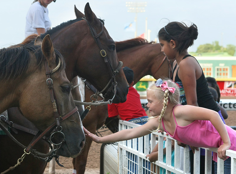 Riley Yates pets a horse after a race at Remmington Park Saturday. PHOTO BY MAIKE SABOLICH