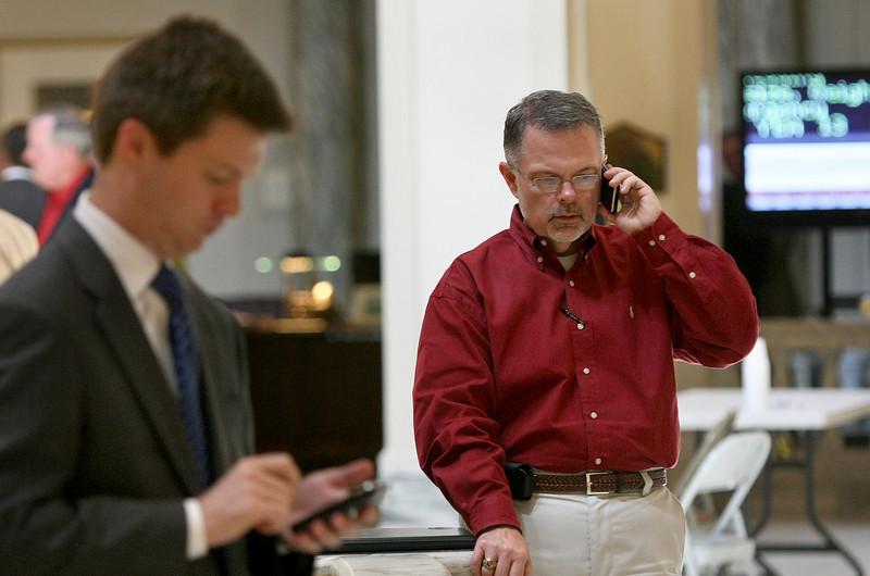 Trent Baggett with the District Attorney's Council, right, talks on the phone on the fourth floor rotunda Friday. PHOTO BY MAIKE SABOLICH