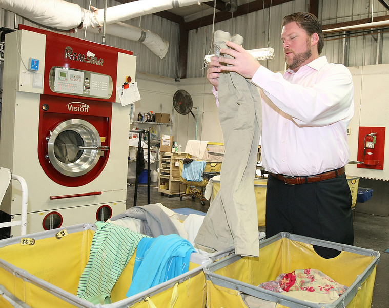 Rusty Bromagen of Best Cleaners in Oklahoma City, one of two cleaners in the state with the entire plant certified as green by the national Green Cleaners Council, sorts through laundry at his facility Wednesday. PHOTO BY MAIKE SABOLICH