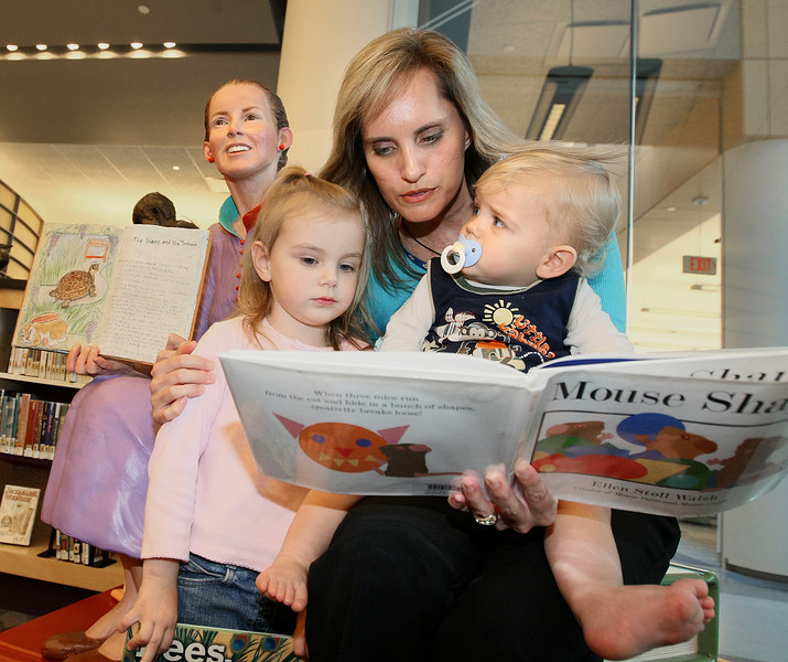 Rondia Banks, children's librarian at Downtown Library, reads a story to Addison and Micah Todd Monday. PHOTO BY MAIKE SABOLICH