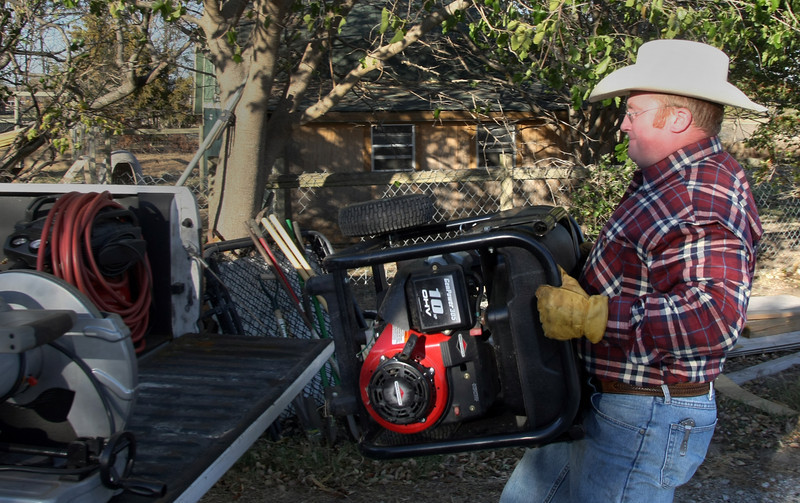 Travis Potts, Owner of Circle P Livestock Company, loads tools to build fences on his property.  Potts intends to provide locally raised organic meat to Tulsa area consumers.