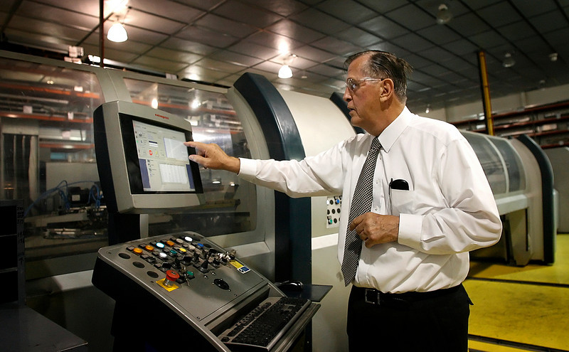 Aaon President and Chief Executive Norman H. Asbjornson demonstrates an automated sheet metal cutting and bending machine at the Tulsa location. Aaon announced an 11% third quarter increase in sales but a net income decrease of 32% for the quarter.