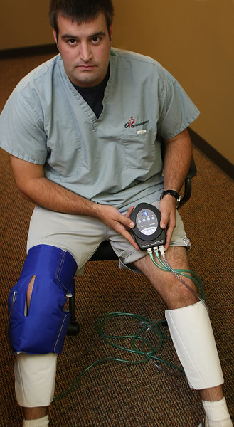 Kayle Anderson, Patient Care Technician, demonstrates the Triple Play VT vascular therapy system developed by Mark Farrow of Tulsa.