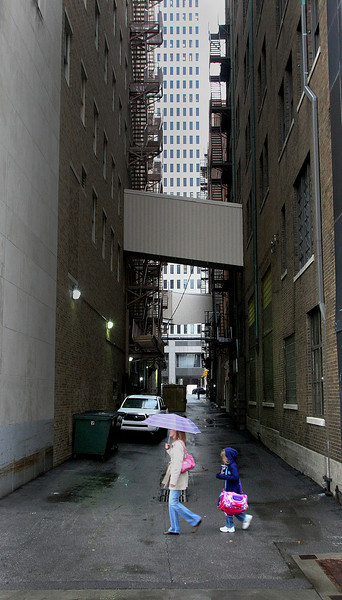 Mother and Daughter hustle past an alley to avoid the rain in Downtown Tulsa Friday.