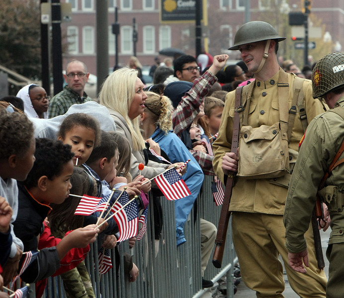 Participants in the Veterans Day parade, which wound through downtown Tulsa, chat with spectators before the parade begins.