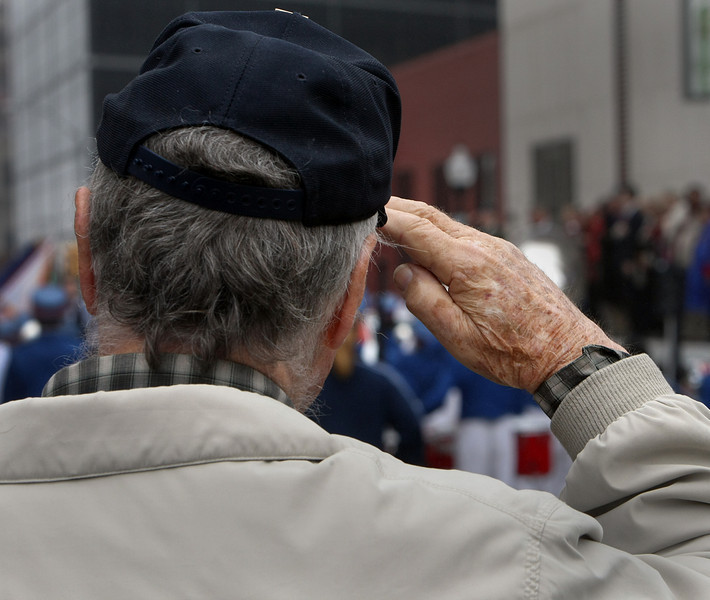 A participant in the Veterans Day parade, which wound through downtown Tulsa, a salute as the national anthem is played.