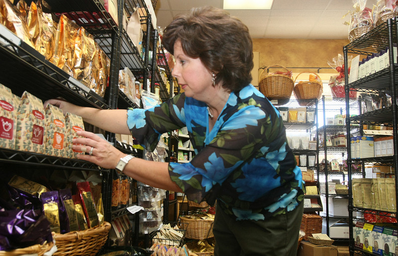 Nancy Edison, store manager at Gourmet Gallery in Edmond, sorts through MIO products at the store Monday. PHOTO BY MAIKE SABOLICH