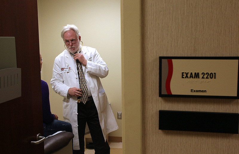 Doctor Charles Foulks consults with a patient visiting his office at the OU Tulsa Schusterman Center Clinic.