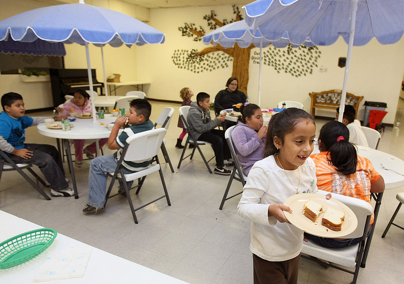 Diana Martinez Yesmin gets jelly peanut butter sandwiches at one of the  Regional Food Bank of Oklahoma's Kids Cafe in Bethany Tuesday.  PHOTO BY MAIKE SABOLICH