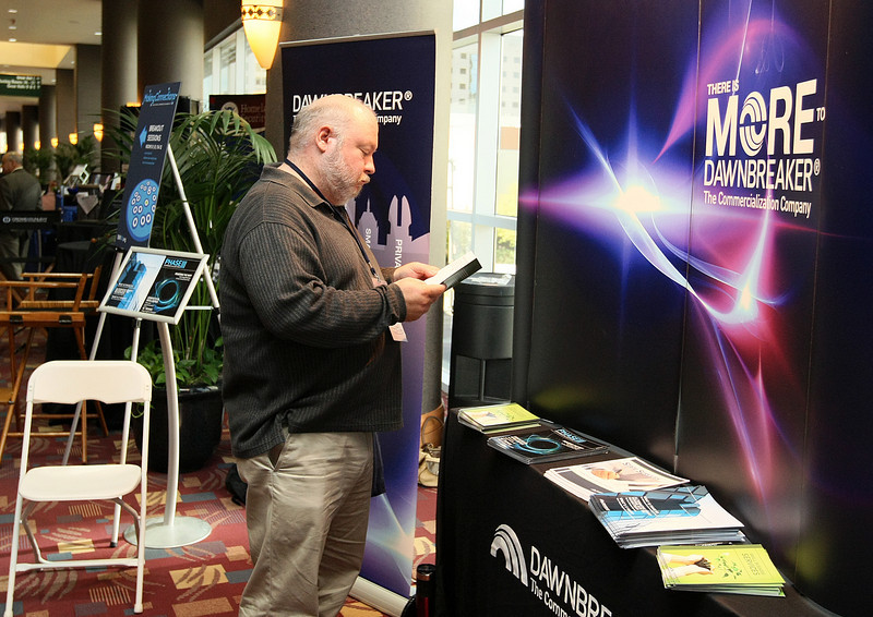 Bruce Queen checks out an exhibit during the SBIR National Conference at the Cox Convention Center Monday. PHOTO BY MAIKE SABOLICH