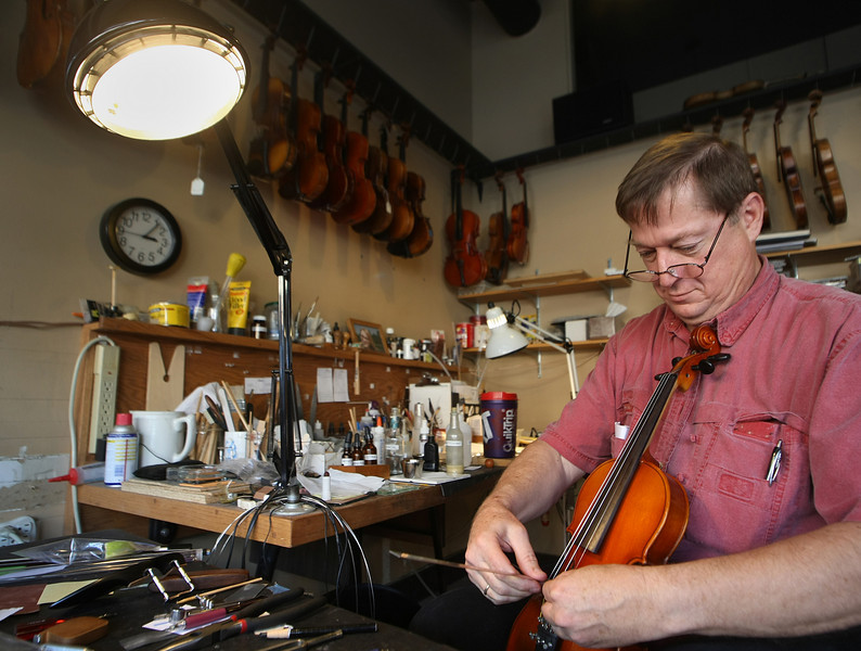 Tulsa Violin Shop employee Phillip Wachowski repairs a violin.  The shop opened in 1996 and is located in the Brady District of Tulsa.