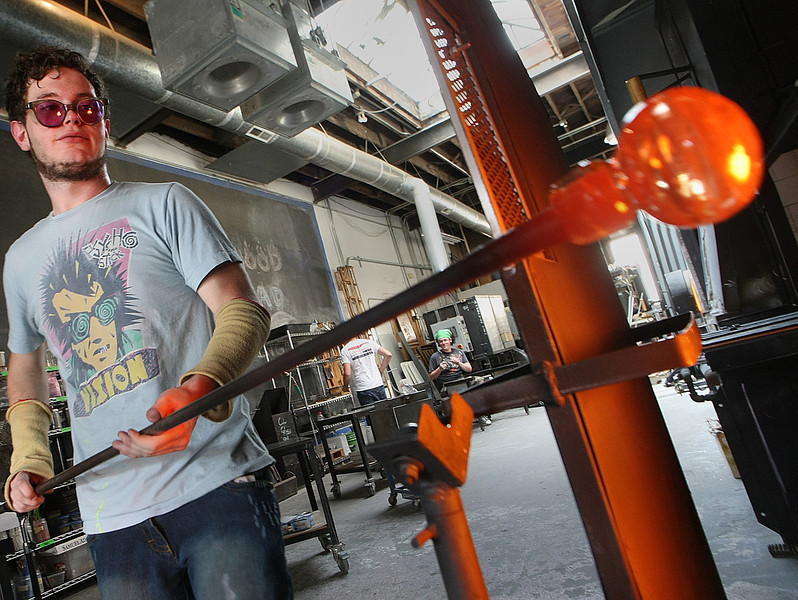 Tulsa Community College student Ely Burgess work on a hand blown vase at the Tulsa Glassblowing Studio located in the Brady Arts District in Tulsa.