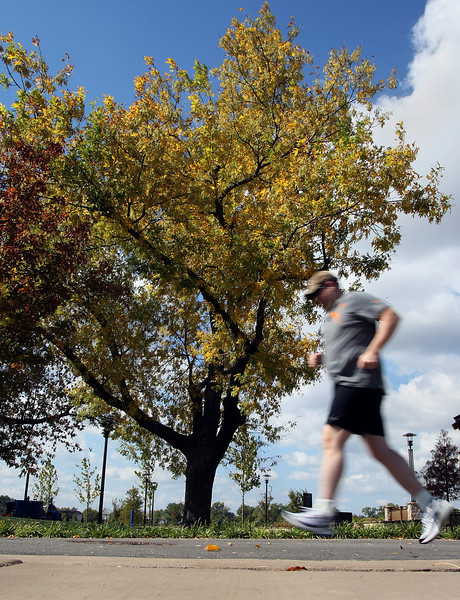 A runner takes advantage of the beautiful weather and gets a mid-day run on the River Parks trail in Tulsa.