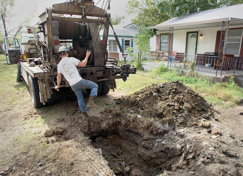 Workmen from P&P Cementing work to cap a 60 year old well that was leaking methane from underneath a residential driveway in North Tulsa.