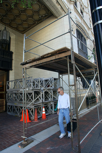 A pedestrian walks through scaffolding erected around the Mid-Continent Building in downtown Tulsa. Contractor Mark 1 of Chicago should begin long-discussed terra cotta repairs to the Mid-Continent Tower next week.