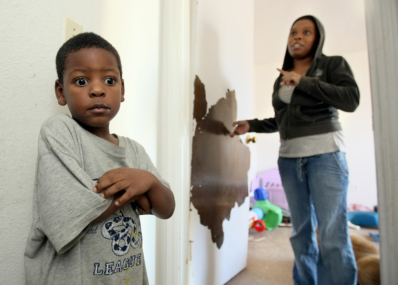 Lamarius Alexander, 4, hangs out in the hallway as his mother, Ashley Alexander, shows the paint peeling off the door to the children's room at the family's apartment at Wentwood at Macarthur Thursday. Alexander says she has seen her children run around with supposedly lead-based paint chips of their faces. PHOTO BY MAIKE SABOLICH