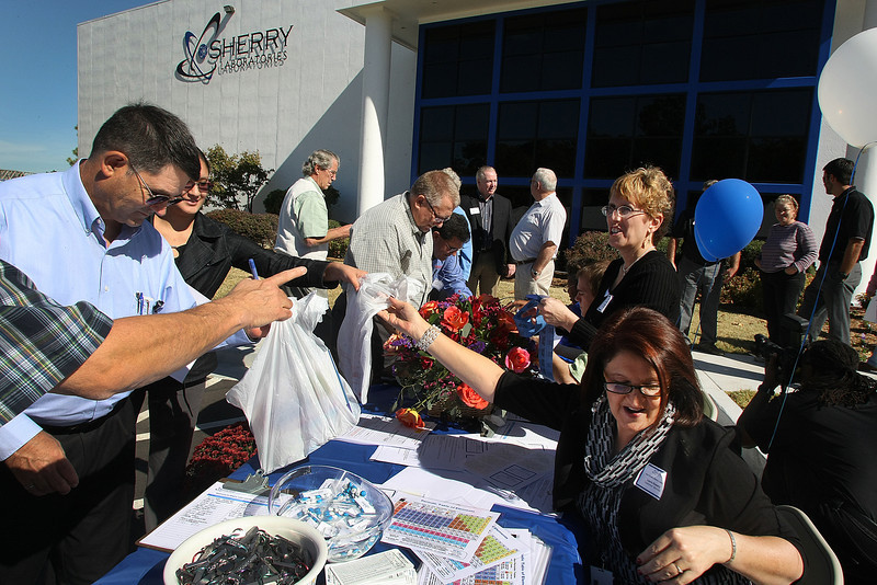 Participants score a goodie bag while lined up to register at the Sherry laboratories open house in Broken Arrow Thursday.
