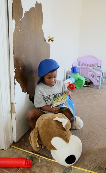 Lamarius Alexander, 4, looks at a book in the doorway to his room at the famaily's apartment  at Wentwood at Macarthur Thursday. His mother, Ashley Alexander,  says she has seen her children run around with supposedly lead-based paint chips of their faces. PHOTO BY MAIKE SABOLICH