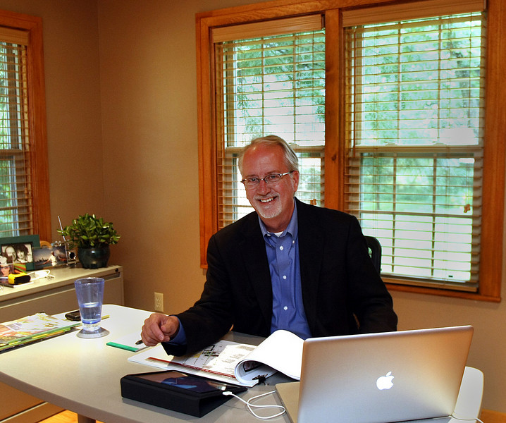 Michael Birkes pauses for a photo at his home office in Tulsa.