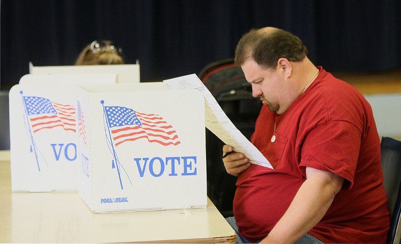 Chris Hewes, right, studies the ballot at Crown Heights Christian Church Tuesday. PHOTO BY MAIKE SABOLICH