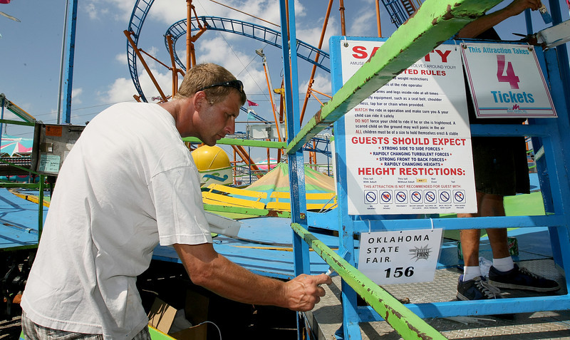 Billy Winn puts the finishing paint touches on the entrance to a ride at the Oklahoma State Fair before the gates open to the public Friday. PHOTO BY MAIKE SABOLICH