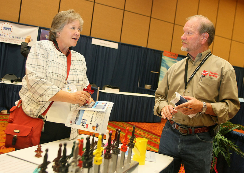 Debbie Cox visits with James Moore with Topps Powder Coating, a vendor at the Oklahoma Manufacturing Alliance conference Tuesday in Norman. PHOTO BY MAIKE SABOLICH