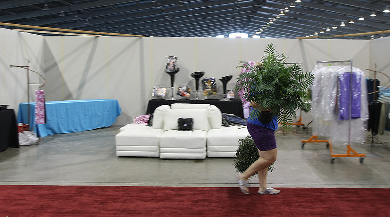 Pallas Cleary moves plants in to set up the MIX 96 display at the House Beautiful show this weekend at the fairgrounds in Tulsa.
