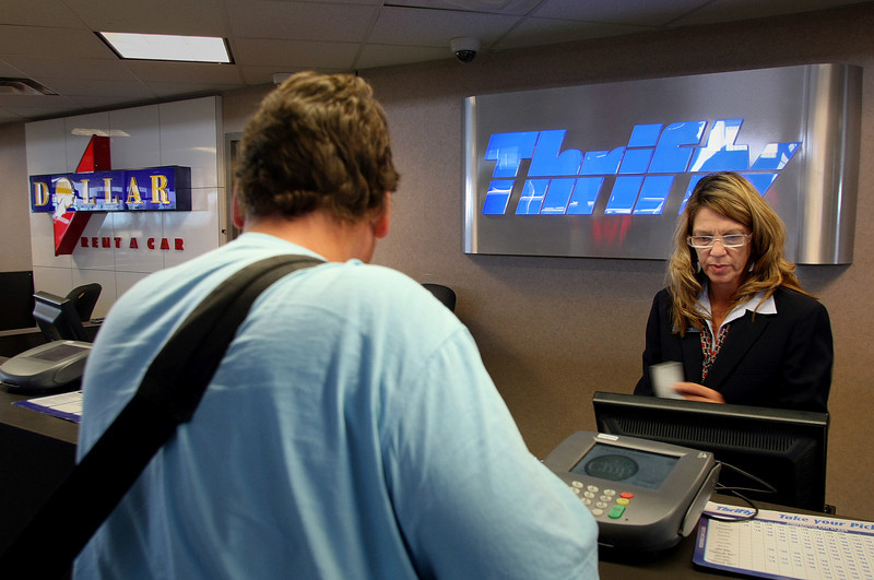Dollar Rental Car employee Rhonda Coats chats with a traveler from Dallas while renting him a car at the Tulsa International Airport.