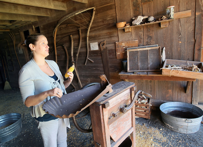 Nancy Coggins, interim executive director at the Harn Homestead, explains a machine the pioneers used to get the kernels off corn cobs. PHOTO BY MAIKE SABOLICH