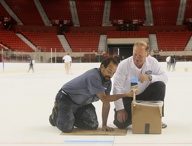 XXX,XXX, right, discusses with Juan Nazario, building service technician, the application of the color to the ice. PHOTO BY MAIKE SABOLICH