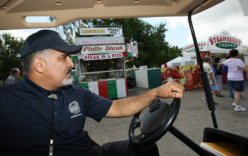 Sasan Pilehvar, health inspector and special events coordinator for the Oklahoma City-County Health Department, makes his rounds in a golf cart at the Oklahoma State Fair. PHOTO BY MAIKE SABOLICH