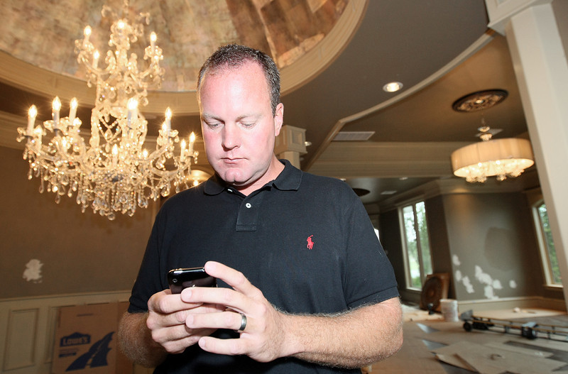 Steve Allen, chairman of the 2010 Parade of Homes, plays with his iPhone at the Parade of Homes show House on 13300 Canyon Lakes Drive Wednesday. Parade of Homes has come out with an iPhone application to facilitate navigation to the homes and feedback on the projects.  PHOTO BY MAIKE SABOLICH