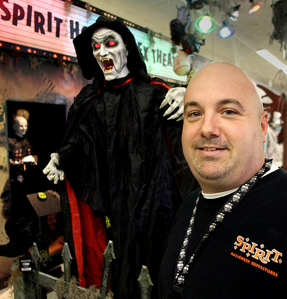 Jeff Wood, Regional Manager of Tulsa Spirit Halloween store, pauses for a photo with a few of spookier items for sale in his shop.