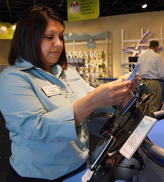 Rosie  Reyes, US Cellular Wireless Consultant at the Tulsa Hills Shopping Center store in Tulsa, places information cards announcing the companies new XXXXXXX OOOOOO.
