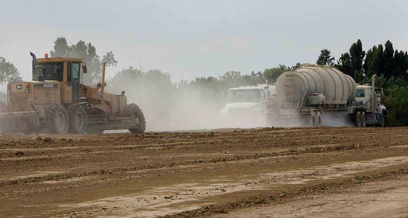 Trucks dispose of fly ash in the containment area as a water truck wets the ash to keep it from blowing in the wind t the PSO electric generation plant in Oologah.