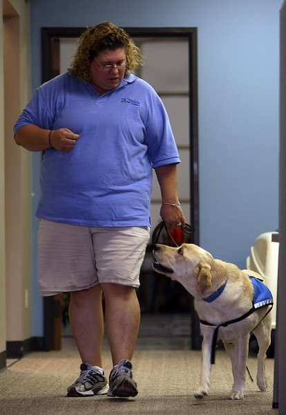 Harmony McDaniel, a trainer for Therapetics in Tulsa, works to train a service dog.