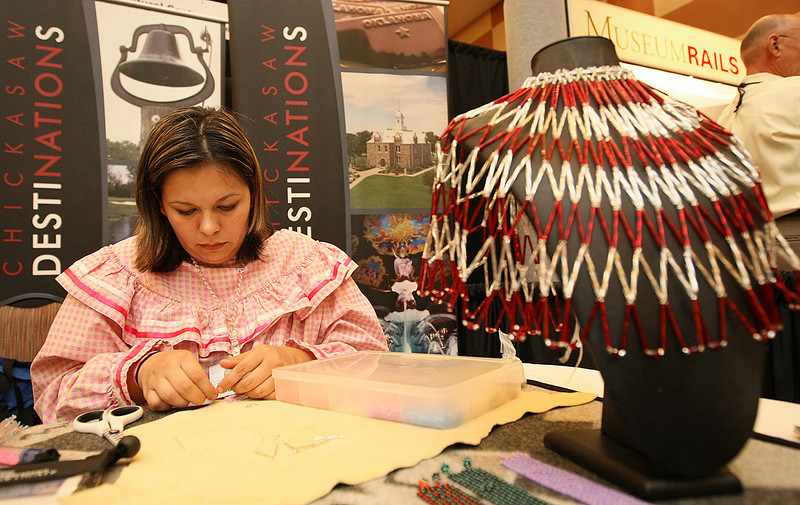Tashina Hamilton with the Chickasaw Nation makes bead earrings during the American Association for State and Local History and the Oklahoma Museum Association's national conference Wednesday at the Cox Convention Center. PHOTO BY MAIKE SABOLICH