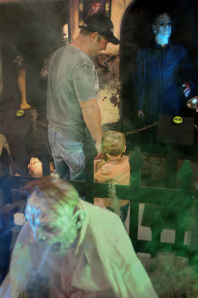 Holding on to his fathers hand Jackson Roumbanis stays close to his Father Fred while looking at a few of spookier items for sale in the Spirit Halloween Store in Tulsa.