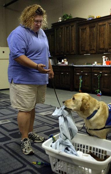Harmony McDaniel, a trainer for Therapetics in Tulsa, works with a service dog while training her to help with the laundry.