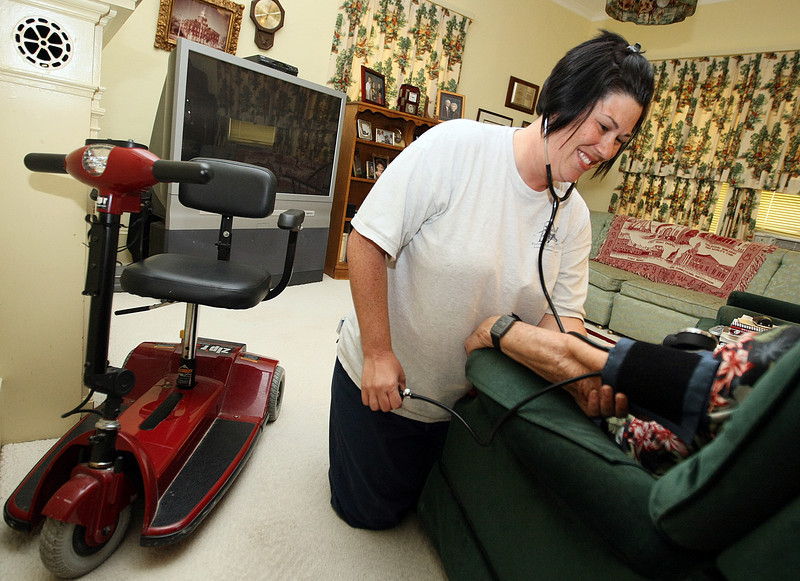 Kimberly Hall, nurse and bereavement coordinator with Russell-Murray Hospice, measures a patient's blood pressure Tuesday at the patient's home in El Reno. PHOTO BY MAIKE SABOLICH