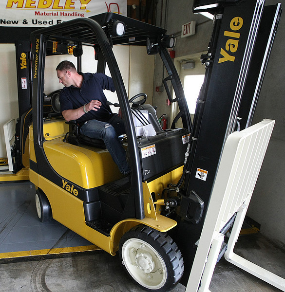 Shannon O'Banion, Major Accounts Manager at Medley material Handling, backs a new forklift into position at the companies Tulsa warehouse.