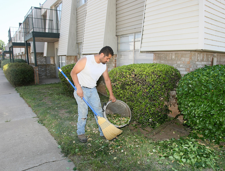 Carlos Rivera cleans up leaves at Overlake Apartments at 7920 NW 21rst Street. PHOTO BY MAIKE SABOLICH