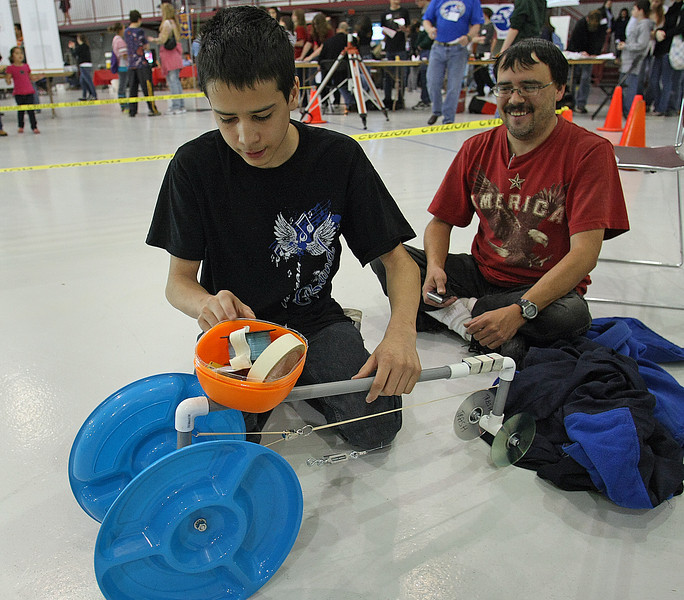 Jeffrey Jackson and his father Zach work to get Jeffrey's entry into the rubber band powered car race ready for entry at the Tulsa Technology Centers Engineering Challenge in Jenks.