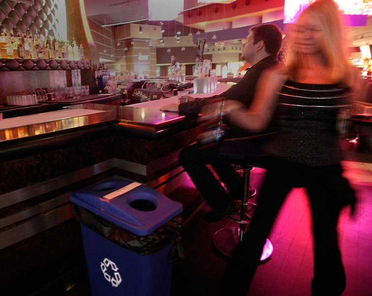 Angela DeSautell deposits a beer bottle in the recycling bin used at the Hard Rock Café.
